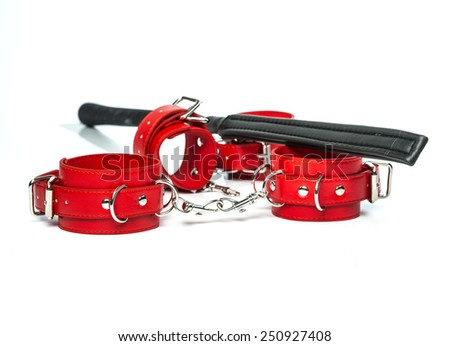 Stuff for sexual role playing: black whip or flogger made of black leather and red hand cuffs. - stock photo