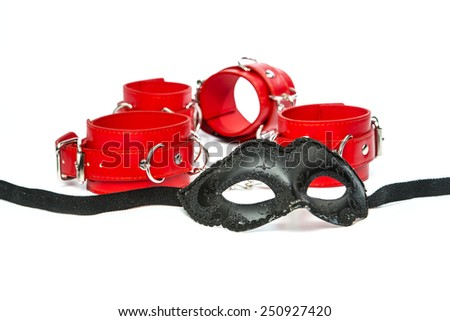 Stuff for sexual role playing: fetish mask in venetian style together with red hand cuffs. - stock photo