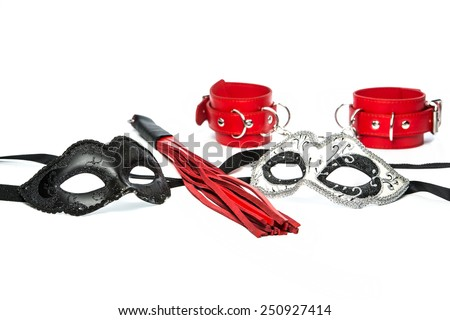 Stuff for sexual role playing: fetish masks in venetian style together with a whip made of red leather and red hand cuff made of leather - stock photo