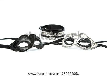 Stuff for sexual role playing: fetish masks in venetian style together with collar made of black leather and decorated with steel - stock photo