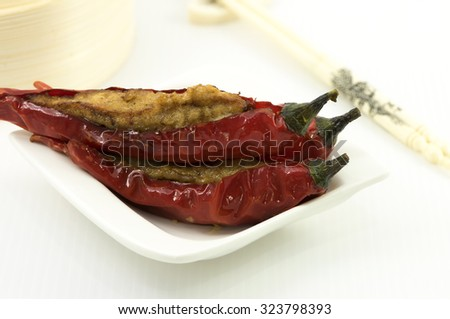 Stuff red chillis with minced meat mix with fish paste. A dim sum style Chinese cuisine prepared as small bite-size portion of food traditionally served in small steamer basket or on small plate.
