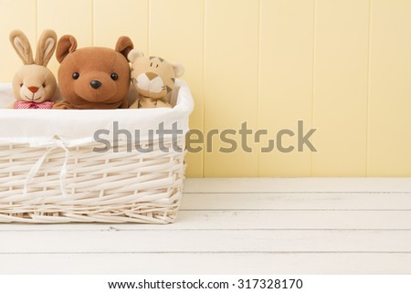Stuffed animal toys in a basket on the floor - stock photo