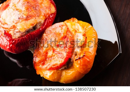 Stuffed bell peppers with chopped meat, cheese and tomato on black plate - stock photo