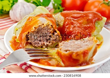 Stuffed cabbage meat in cabbage leaves with tomato sauce and a fork on a plate on a napkin, tomatoes, parsley and garlic on a background of pale wooden plank - stock photo