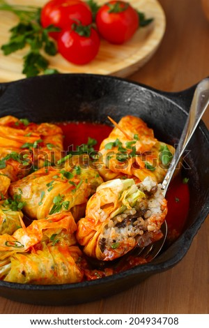 Stuffed cabbage rolls with rice and mushrooms in tomato sauce. Dolma, sarma, or golubtsy - traditional dish of many countries