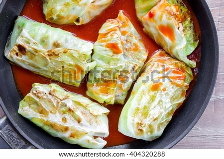 Stuffed cabbage with meat, quinoa, veggies, delicious rolls, Russian dish with tomato sauce - stock photo