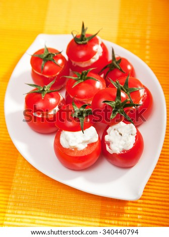 Stuffed cherry tomatoes with cheese cream, served in a plate, ready-to-eat
