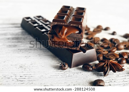 Stuffed chocolate with coffee beans on wooden table, closeup - stock photo