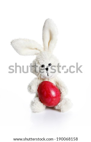 Stuffed easter bunny with red Easter egg - stock photo