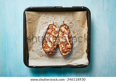 Stuffed eggplant on baking sheet and blue wooden table - stock photo