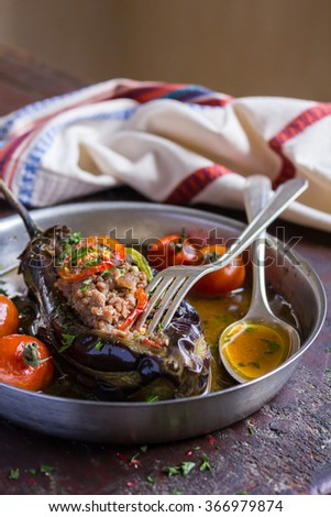 Stuffed eggplant or aubergine with minced meat, carrot, onion, cherry tomatoes, pepper in a pan, traditional turkish cuisine, selective focus - stock photo