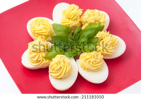 stuffed eggs with mayonnaise on a red plate - stock photo