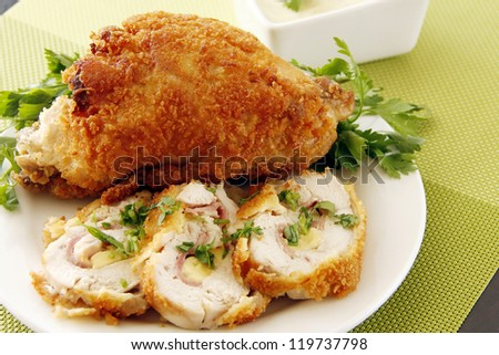 Stuffed golden fried chicken garnish with vegetables - stock photo