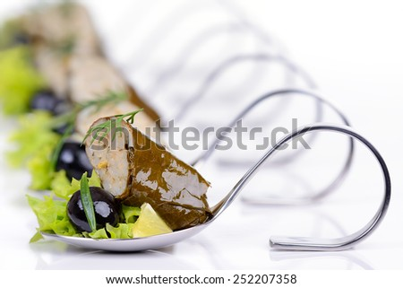 Stuffed grape leaves with black olives on appetizer spoons - stock photo