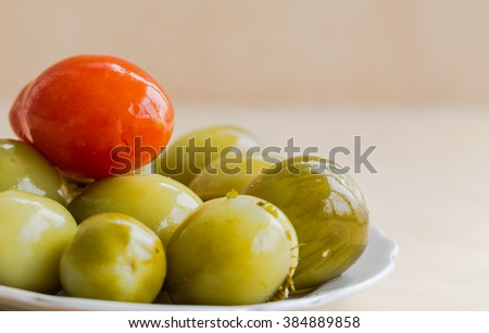 Stuffed green tomatoes with red tomato on white plate.