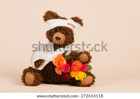 Stuffed hand made bear with pain plaster and flowers isolated over white background - stock photo