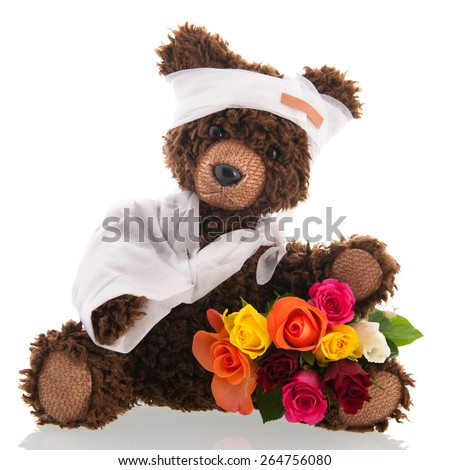 "Stuffed hand made poorly bear with plaster and flowers for ""Get well soon"" isolated over white background - stock photo"
