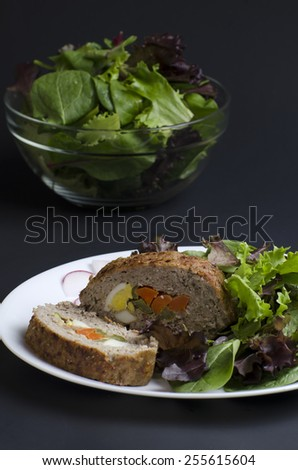 Stuffed meatloaf and green salad - stock photo