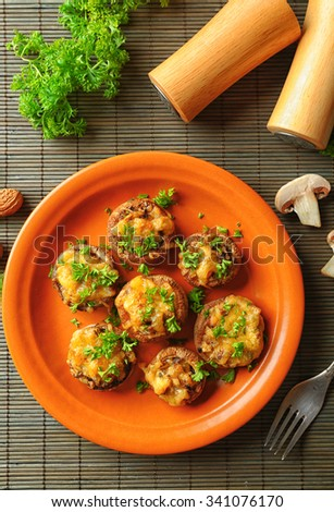 Stuffed mushrooms on plate, on table background