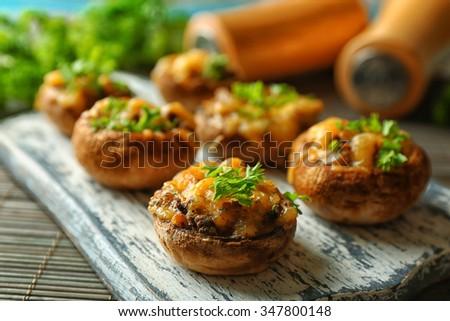Stuffed mushrooms on wooden board, on table background - stock photo