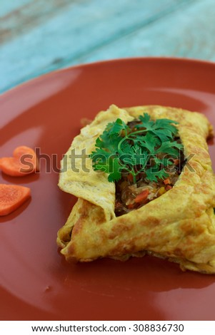 stuffed omelette, Omelet with vegetable salad and Heart-shaped carrot, on blue old wooden