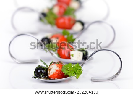 Stuffed peppers, black olives and feta cheese on appetizer spoons - stock photo