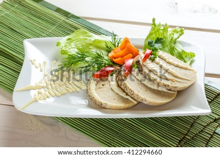 Stuffed pike fish - sliced on white plate with parshley, salad, carrot - stock photo