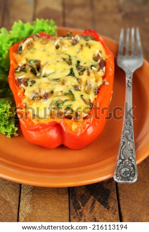 Stuffed red pepper with lettuce on plate on wooden table  - stock photo