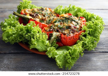 Stuffed red peppers with greens on plate on wooden table - stock photo