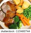 Stuffed roast pork dinner with vegetables and gravy. - stock photo
