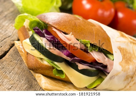 Stuffed sandwich with ham,cheese and vegetables on the wooden table.Selective focus on the sandwich - stock photo