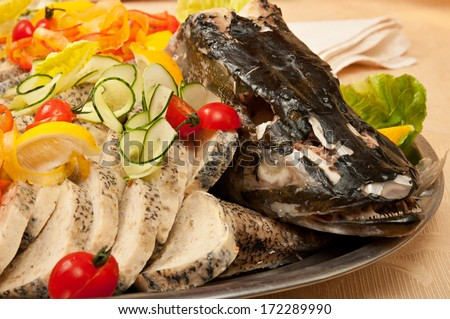 Stuffed sliced pike with head, decorated with tomato, lemon and cucumber close up in restaurant - stock photo