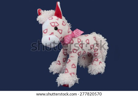 stuffed soft funny pink toy horse over purple background. Horse is decorated with pink dotted bow and red hearts over its body. Background is purple  - stock photo