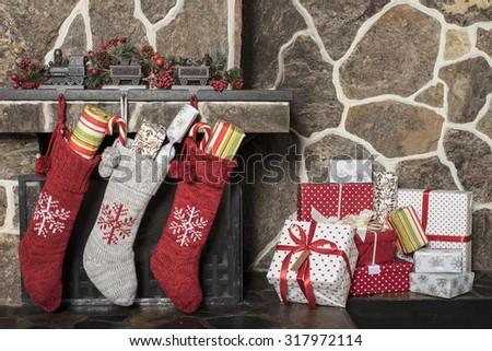 Stuffed stockings hanging on a fireplace on christmas morning - stock photo