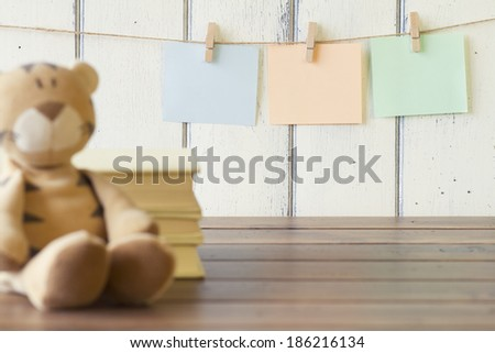 Stuffed tiger toy with three sheets of paper hanging on clothespins. Robin egg blue background and three books. Vintage look. - stock photo