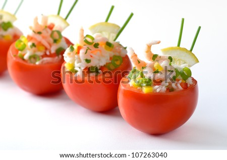 Stuffed tomatoes with shrimps, rice, bell peppers, spring onions, lemon, chives and parsley. A very delicious cold appetizer - stock photo