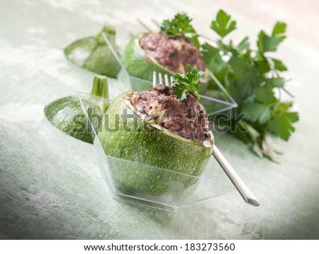 stuffed zucchinis on glass over green backgrond - stock photo