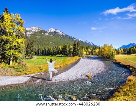 Stunned woman performing yoga in a white shirt on a rocky shoal creek. Autumn day in the Canadian Rockies, Banff Park - stock photo