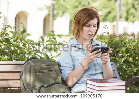 Stunned Young Pretty Female Student Outside with Backpack and Books Sitting on Bench Texting on Cell Phone. - stock photo