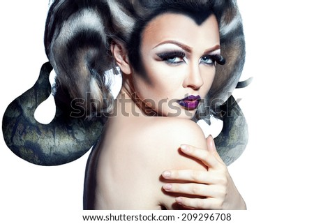 Stunning adult female with creative horns in head looking at camera on white background - stock photo