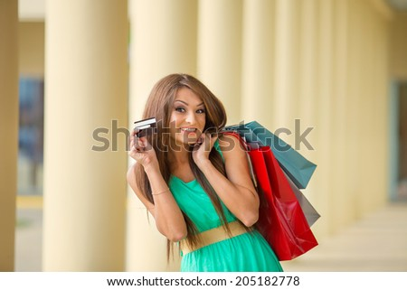 stunning and very beautiful woman in dress with long brown hair holding card and colored shopping bags - stock photo
