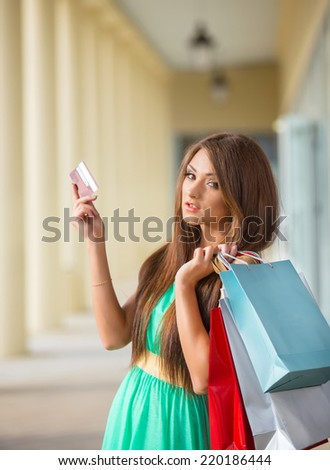 stunning and very beautiful woman in dress with long brown hair holding credit card and colored shopping bags - stock photo