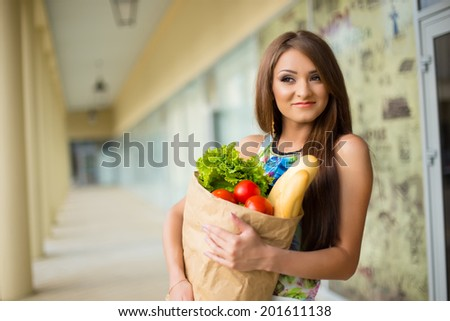 stunning and very beautiful woman in dress with long brown hair holding food in bag near shop - stock photo