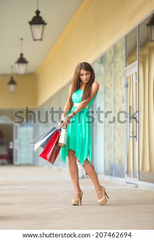 stunning and very beautiful woman in dress with long brown hair with colored shopping bags