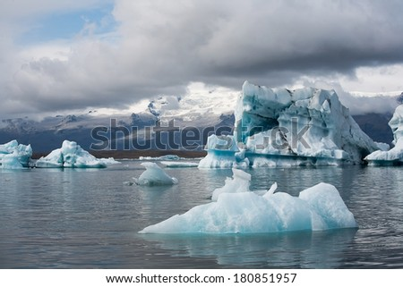 Stunning atmosphere of huge iceberg reflecting in the cool glacial water.