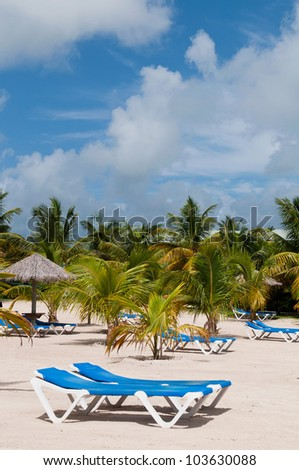 stunning beach with chairs and coconut umbrella on a tropical resort in Antigua (gorgeous blue sky with clouds)