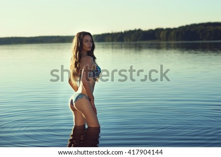 Stunning beautiful girl posing in blue bikini in the lake. Young sexy woman. Full length portrait at sunset with soft lightning - stock photo