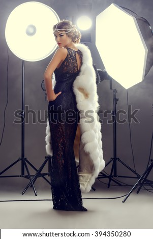 Stunning beauty model posing at studio in light flashes. Professional fashion model. Celebrity. Full length portrait.