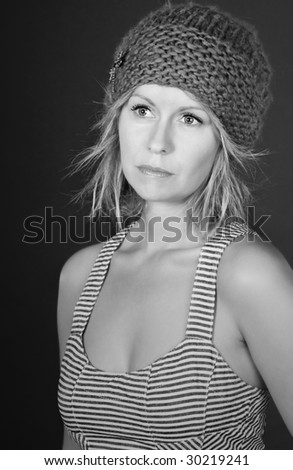 Stunning Black and White Shot of a Beautiful Blonde Girl in Hat against Grey Background - stock photo