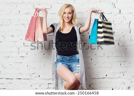 Stunning blond girl against the wall presenting  shopping bags with new purchases wearing summer clothes. - stock photo